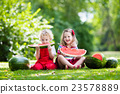 Kids eating watermelon in the garden 23578889