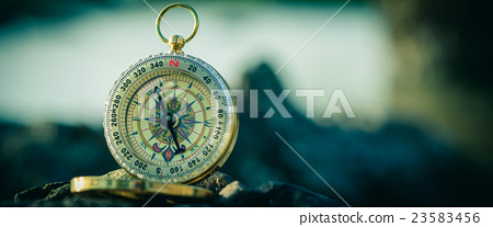 Analogical compass abandoned on the rock 23583456