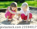 Two little sisters playing in a sandbox 23594017