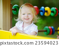 Little girl having fun at a playground 23594023