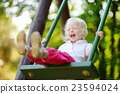 Adorable girl having fun on a swing 23594024