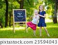 Two excited little sisters by a chalkboard 23594043