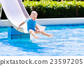 Little child on water slide in swimming pool 23597205