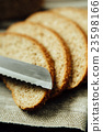 Sliced bread and knife on linen cloth 23598166