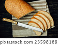 Sliced bread and knife on linen cloth, black table 23598169