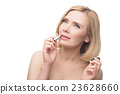 Beautiful middle aged woman applying lipstick 23628660