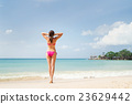 Young woman in a swimsuit posing on the beach 23629442
