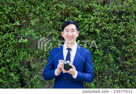 Smiling Asian professional photographer and camera 23677012