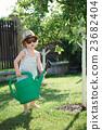 little boy watering trees in summer garden 23682404