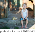 boy with little yellow duckling in summer village 23683643