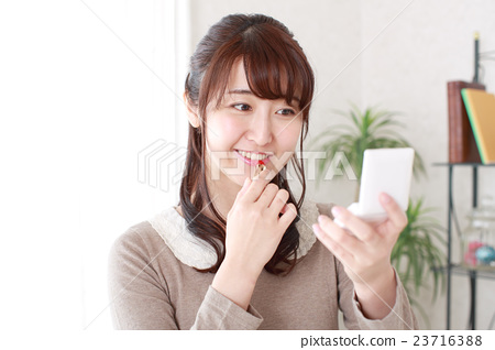 A girl painting lipstick 23716388
