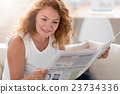 Positive adult woman reading newspaper 23734336
