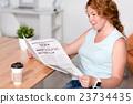 Pleasant woman reading newspaper 23734435