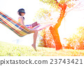 Woman on hammock reading a book in spring 23743421