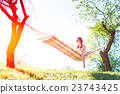Woman sitting on a hammock reads a book 23743425