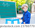 Little boy at blackboard practicing math 23760770