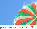 Parasailing, beach umbrella on sky background 23776910