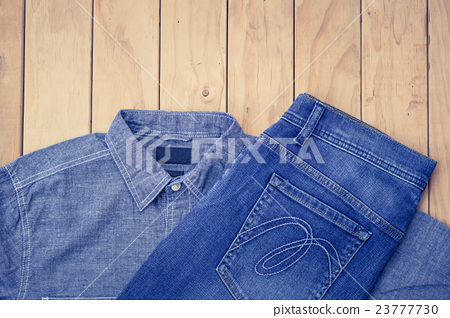Blue jeans on wooden background top view 23777730