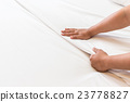 Hand set up white bed sheet in hotel room 23778827