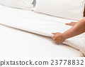 Hand set up white bed sheet in hotel room 23778832