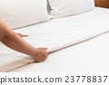 Hand set up white bed sheet in hotel room 23778837