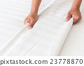 Hand set up white bed sheet in hotel room 23778870