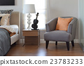 modern bedroom with orange pillow on grey chair 23783233