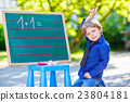 Little boy at blackboard practicing math 23804181