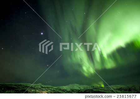 Strong green aurora northern lights over mountain 23815677