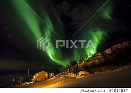 Strong green aurora northern lights over mountain 23815687
