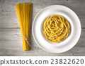 Raw and cooked spaghetti on the wooden table  23822620