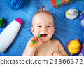 Baby lying on towel with washing tools 23866372