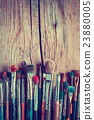 Row of artist paintbrushes closeup on wood 23880005
