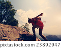 youngwoman hiker climbing rock on mountain peak 23892947