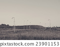 Many streetlamps on a meadow 23901153