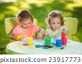 Two-year old girls painting with poster paintings 23917773