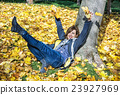 Crazy young woman throwing yellow leaves in autumn 23927969
