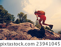 youngwoman hiker climbing  on mountain peak cliff 23941045