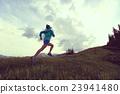 woman trail runner running on mountain peak 23941480