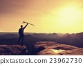 Tourist with poles in hands stand on rock  23962730