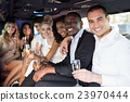 Well dressed people drinking champagne in a limousine 23970444