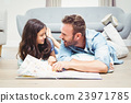 Daughter and father with picture book lying on floor 23971785