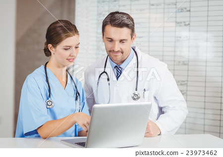 Doctor and colleague working on laptop while discussing 23973462