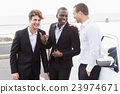 Well dressed people posing next to a limousine 23974671
