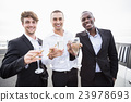 Well dressed men drinking champagne next to a limousine 23978693