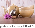 Wooden spoon full of dry tea and tea set 23987422
