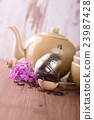 Wooden spoon with pile of dry tea and tea set 23987428