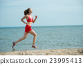 Young lady running at the sunny summer sand beach 23995413