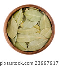 Dried bay leaves in a bowl on white 23997917