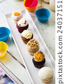 Colorful delicious cupcakes in row on plates 24037151